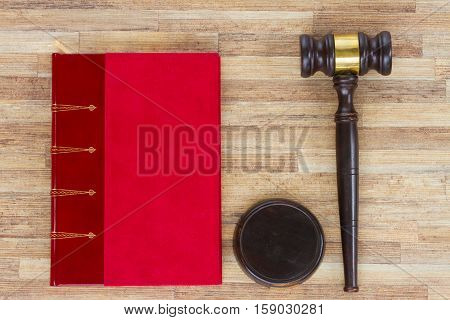 Wooden Law Gavel and red legal book on wooden desktop, top view