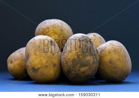 fresh unwashed unpeeled potatoes closeup macro black bagkground