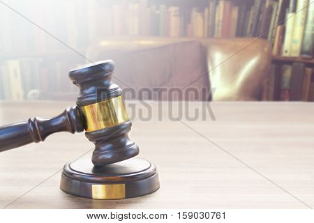 Wooden Law Gavel against a row of law books on wooden desktop