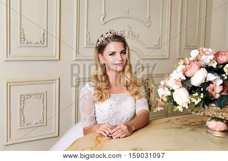 Beautiful blonde woman wearing gorgeous dress and crystal crown posing in luxury classic apartment