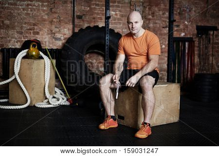 Young sportsman with skipping rope sitting on jump box in gym