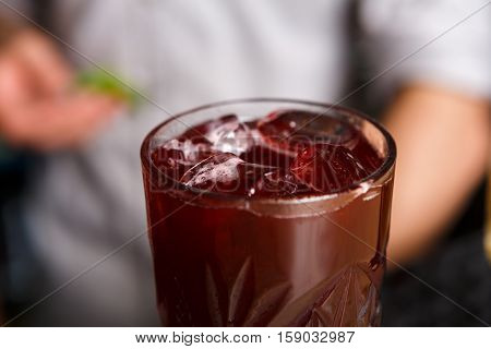 Closeup of healthy sweet berry non-alcoholic party cocktail at restaurant background. Refreshing drink with ice