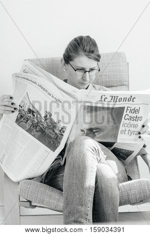 PARIS FRANCE - NOV 29 2016: Woman reading Le Monde newspaper with headline and articles about Fidel Castro Cuban President - dead on November 25 2016 - black and white