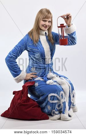 young smiling snow maiden holding a lamp