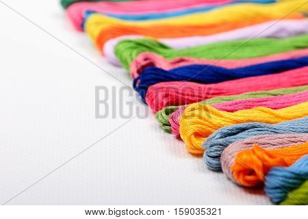 Colorful cotton craft threads on white canvas with copy space