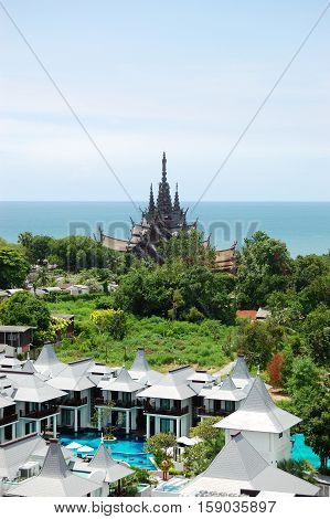 Modern luxury hotel and Sanctuary of Truth temple at background Pattaya Thailand