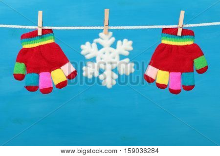 Gloves with snowflake hanging on the clothesline on blue wooden background