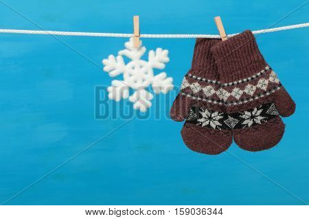 Mittens with snowflake hanging on the clothesline on blue wooden background
