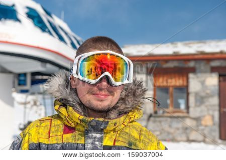 Young man in ski goggles outdoors with ski lift station in mountains at background. Val-d'Isere, France