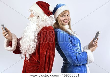 Cheerful Santa Claus with the snow maiden posing with smartphones