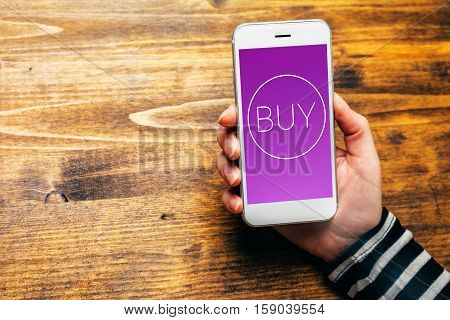 Using mobile wallet to purchase items in online shopping female hand holding smartphone with BUY icon generated