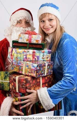 Santa Claus and snow maiden holding a Christmas gift
