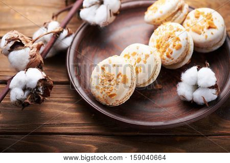 Creme brulee macaroons at a ceramic plate and cotton flowers on a wooden table. Soft light. Close view.