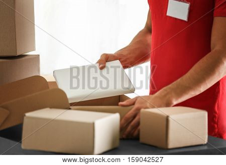Courier putting parcel in carton box