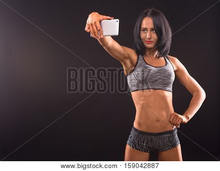Sports, fitness, bodybuilding concepts. Bodybuilder woman posing with her hand on hip and holding mobile or smart phone in front of her. Pretty fitness lady making self photos.