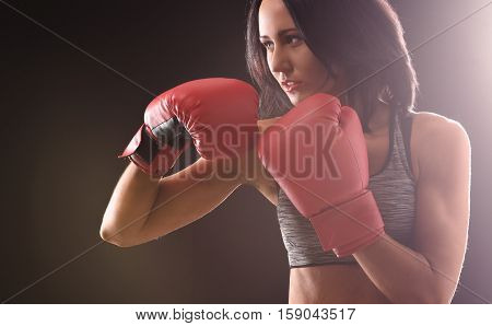 Boxing concept. Boxer and fitness woman ready for fight or battle with red gloves on over black background in studio.