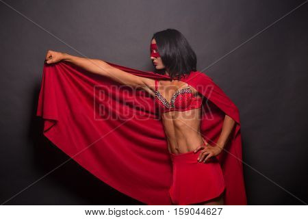 Picture of young super hero woman in red super hero costume over grey background in studio. Super hero lady ready to save world.