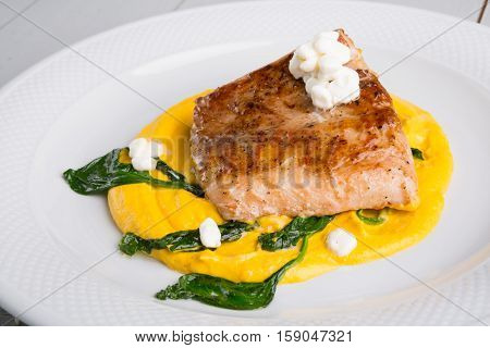 Fried fish fillet with yellow humus garnish