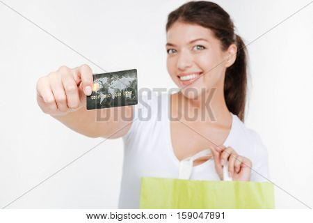 Picture of happy young woman dressed in white t-shirt holding purchasings and credit card after shopping. Isolated over white background. Look at camera. Focus on credit card.