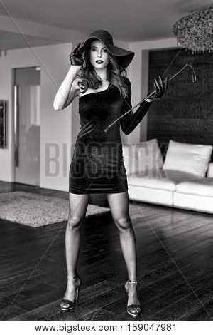 Sensual strict dominatrix lady in hat and whip posing indoor black and white