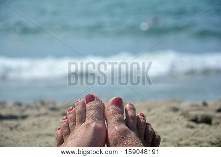 Sandy feet with red toenails on the beach with blurred sea in the background