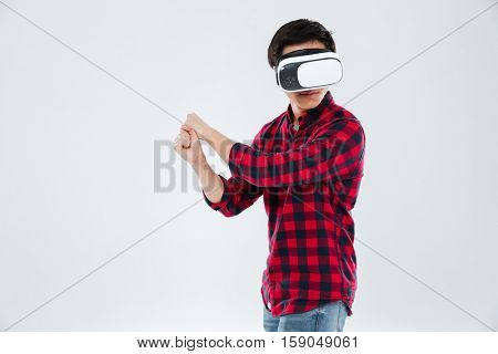 Photo of young asian man dressed in casual shirt in a cage and wearing virtual reality device and holding an imagine tennis racket. Isolated over white background.