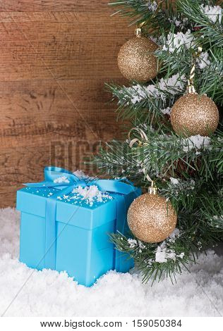 Blue gift box in snow by a Christmas tree with a wood background