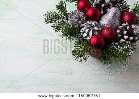 Christmas background with red ornaments silver and snowy pine cones. Christmas table centerpiece with silver decor. Copy space.