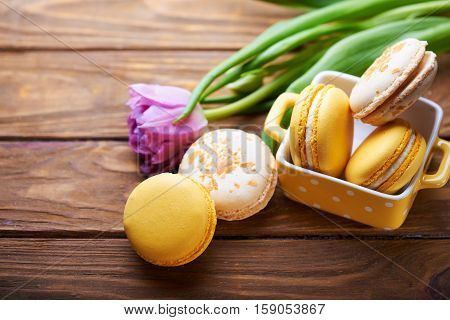 orange and creme brulee macaroons in yellow vase with purple tulip on a wooden table. Soft light. Close view.