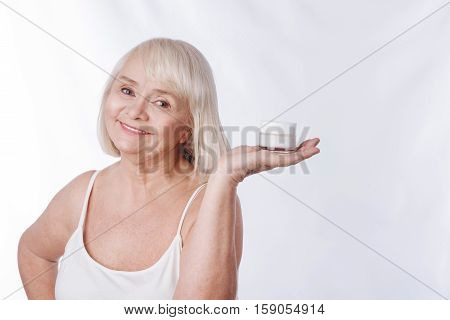 I care about my appearance. Nice optimistic aged woman smiling and holding a bottle of moisture cream while fighting with wrinkles