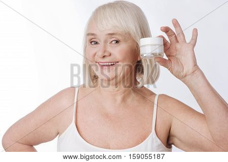 Taking away wrinkles. Positive cheerful senior woman smiling and looking at you while holding an anti age cream bottle