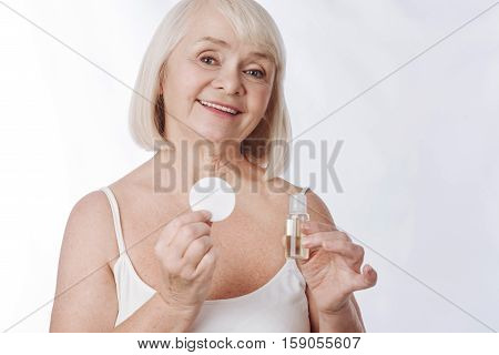 Skin cosmetics. Good looking joyful elderly woman holding a bottle with lotion in one hand and a cotton pad in the other while caring about her skin