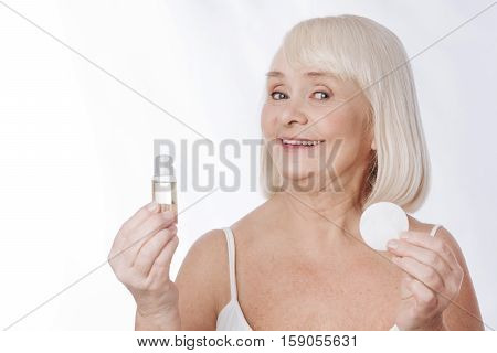 Skin moisturizer. Nice optimistic aged woman holding moisturizing lotion and having a cotton pad in her hand while standing against white background