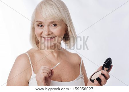 I care about my appearance. Good looking cheerful aged woman holding a small mirror and using a cotton bud while being in a great mood