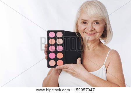 Professional beauty products. Delighted good looking senior woman holding a rouge palette and showing it to you while standing against white background