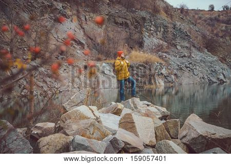 man standing alone and lookin on lake in cloudy autmn day