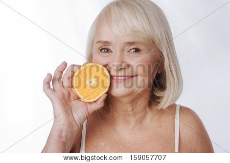 Citrus fruits. Pleasant joyful content woman holding an orange half and squeezing it while looking at you