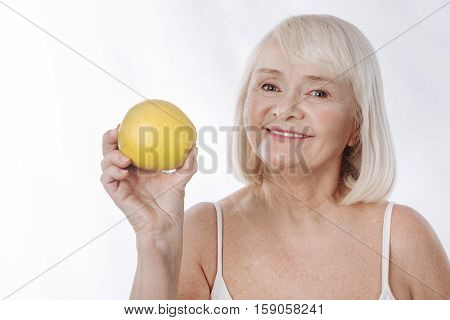 Fruit energy. Nice charming aged woman holding a big yellow apple and smiling while being in a positive mood