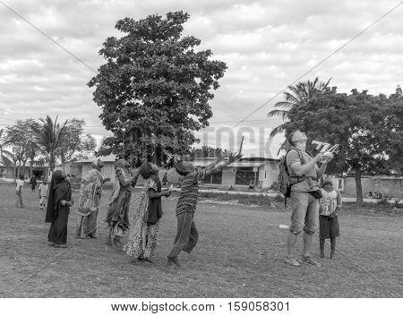 ZANZIBAR, TANZANIYA- JULY 16: european man launching quadrocopter among african childrean July 16, 2016 in Zanzibar. black and white photo