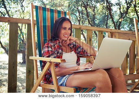Side mid low angle shot of toothy smiling woman who is looking at the screen of the laptop and holding hand on her cheek. Sitting on a comfortable striped summer beach chair