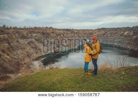 A happy senior couple posing by the lake in cloudy autumn wather