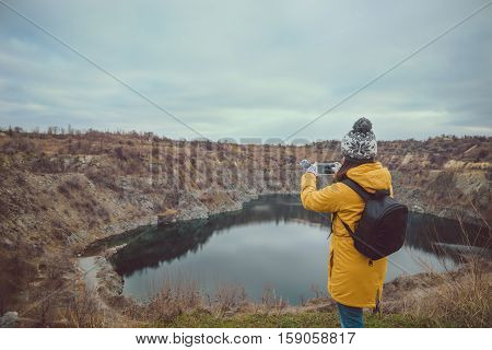 Female hands holding mobile smart phone taking pictures of lake