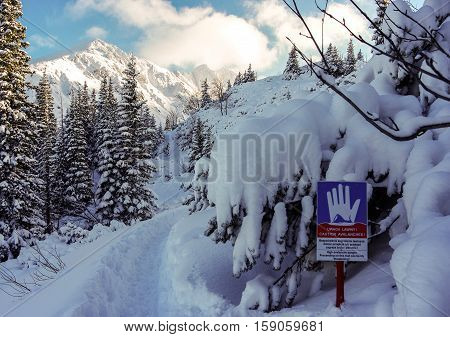 Landscape with a sign warning of the danger of avalanches. Tatry