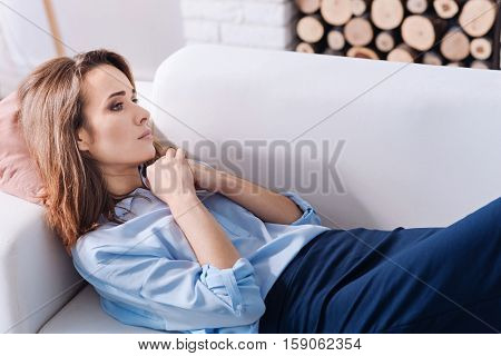 Get some rest. Tired troubled beautiufl woman holding her hands together and lying on the couch while resting at home