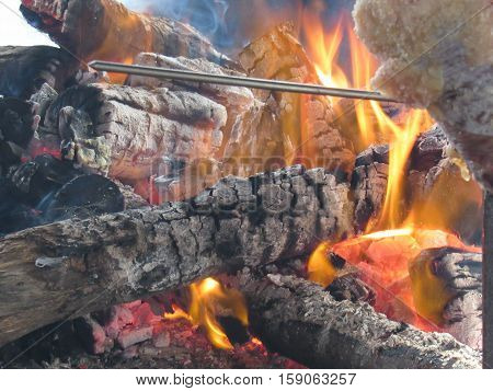 Fire produced by logs thrown to the grill