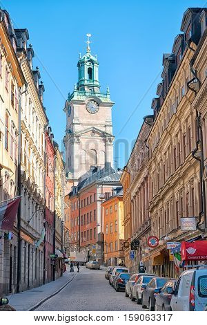 STOCKHOLM, SWEDEN - APRIL 14, 2010: The Storkyrkobrinken Street with restaurants, cafes and shops in Gamla Stan (Old Town). On the background is The Saint Nicolas Church