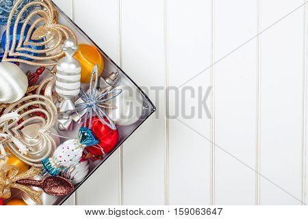 Christmas decoration in the box on the wooden white backround. Winter holidays concept. Space for text.
