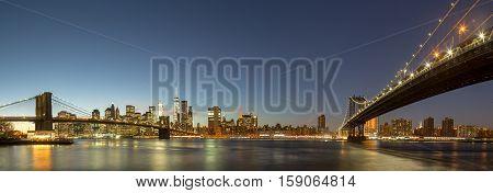 Skyline of Lower Manhattan with Brooklyn Bridge and Manhattan Bridge in the evening