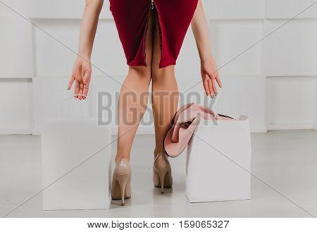 Long female legs in sexy high slit skirt and shopping bags with copy space against modern white wall back view . Shopping Retail