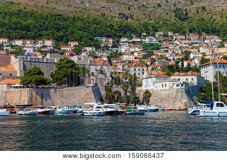 A view across the marina at boats anchored in the harbor and the hillside surrounding the marina at Dubrovnik Croatia.